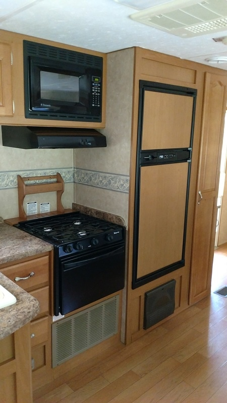 galley kitchen stove and fridge